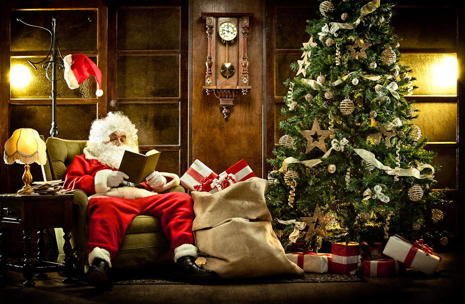 santa claus at home relaxing reading a book near christmas